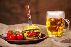 Eigengemaakte rundvleeshamburger en verse groenten op Kleischotel met glas Stock Fotografie
