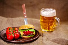 Eigengemaakte rundvleeshamburger en verse groenten op Kleischotel met glas Royalty-vrije Stock Afbeelding