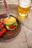 Eigengemaakte rundvleeshamburger en verse groenten op Kleischotel met glas Royalty-vrije Stock Fotografie