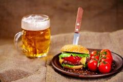 Eigengemaakte rundvleeshamburger en verse groenten op Kleischotel met glas bier op rustieke houten lijst Royalty-vrije Stock Foto