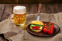 Eigengemaakte rundvleeshamburger en verse groenten op Kleischotel met glas bier op rustieke houten lijst Stock Afbeelding