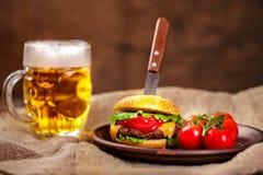 Eigengemaakte rundvleeshamburger en verse groenten op Kleischotel met glas bier op rustieke houten lijst Stock Fotografie