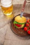 Eigengemaakte rundvleeshamburger en verse groenten op Kleischotel met glas bier op rustieke houten lijst Royalty-vrije Stock Fotografie