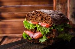 Eigengemaakte Sandwich met zalm en citroen op donkere houten achtergrond Selectieve nadruk Picknickconcept Royalty-vrije Stock Foto's