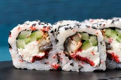 Eigengemaakte sushibroodjes met rode tobikokuiten, komkommer en room che Stock Foto's