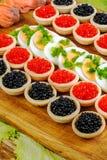 Eigengemaakte tartlets met rode en zwarte kaviaar, zalm, sla en royalty-vrije stock fotografie