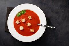 Eigengemaakte tomatensoep met Basilicum, beschuiten en olijfolie op de steenlijst Bereidde een vegetarische schotel op een donker Royalty-vrije Stock Foto