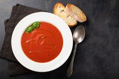Eigengemaakte tomatensoep met Basilicum, toost en olijfolie op de steenlijst Bereidde een vegetarische schotel op een donkere ach Stock Foto's