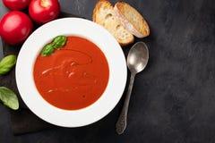 Eigengemaakte tomatensoep met Basilicum, toost en olijfolie op de steenlijst Bereidde een vegetarische schotel op een donkere ach Stock Afbeeldingen