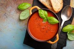 Eigengemaakte tomatensoep met Basilicum, toost en olijfolie op de steenlijst Bereidde een vegetarische schotel op roestig voor Stock Fotografie