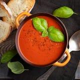 Eigengemaakte tomatensoep met Basilicum, toost en olijfolie op een houten lijst Bereidde een vegetarische schotel op een donkere  Royalty-vrije Stock Afbeeldingen