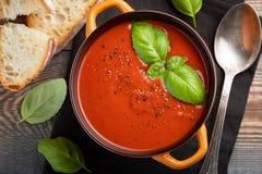 Eigengemaakte tomatensoep met Basilicum, toost en olijfolie op een houten lijst Bereidde een vegetarische schotel op een donkere  Stock Afbeelding