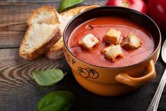 Eigengemaakte tomatensoep met Basilicum, toost en olijfolie op een houten lijst Bereidde een vegetarische schotel op een donkere  Stock Fotografie