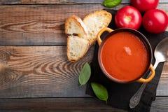 Eigengemaakte tomatensoep met Basilicum, toost en olijfolie op een houten lijst Bereidde een vegetarische schotel op een donkere  Stock Foto's