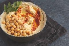 Eigengemaakte traditionele hummus in een kleischotel, donkere achtergrond Hea Royalty-vrije Stock Foto's