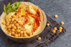 Eigengemaakte traditionele hummus in een kleischotel, donkere achtergrond Hea Royalty-vrije Stock Afbeeldingen