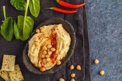 Eigengemaakte traditionele hummus in een kleischotel met spinazie en crac Royalty-vrije Stock Foto's