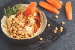 Eigengemaakte traditionele hummus met wortelen in een kleischotel, donkere bedelaars Stock Foto's