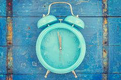 Eigengemaakte turkooise wekker op blauwe houten achtergrond stock fotografie