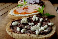 Eigengemaakte Uitgespreide chocolade-Hazelnoot, aardbei en abrikozenjam met verse groene muntbladeren royalty-vrije stock afbeeldingen