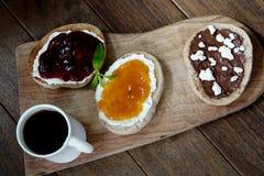 Eigengemaakte Uitgespreide chocolade-Hazelnoot, aardbei en abrikozenjam met verse groene muntbladeren stock foto