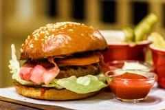 Eigengemaakte verse hamburger met bacon op een houten schotel stock fotografie