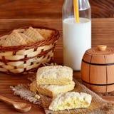 Eigengemaakte vierkante koekjes op een jute en een mand Verse melk in een glaskruik met een stro Kleine houten decoratieve vaatje Royalty-vrije Stock Fotografie