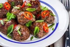Eigengemaakte vleesballetjes met munt, groene uien en Spaanse pepersaus stock foto's
