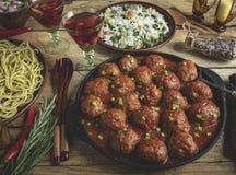 Eigengemaakte vleesballetjes in tomatensaus Pan op een houten oppervlakte, rijst met groenten, deegwaren stock afbeeldingen