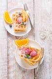 Eigengemaakte wafels met vruchten, stroop en suiker op een witte plaat op een houten achtergrond Stock Afbeeldingen