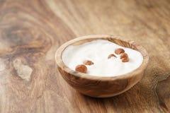 Eigengemaakte yoghurt met hazelnoten in houten kom op houten lijst royalty-vrije stock foto's