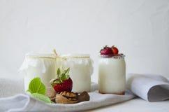 Eigengemaakte yoghurt met verse aardbeien De ingredi?nten voor een gezond ontbijt zijn de helften van aardbeien, okkernoten en yo royalty-vrije stock fotografie
