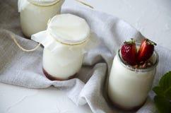 Eigengemaakte yoghurt met verse aardbeien De ingredi?nten voor een gezond ontbijt zijn de helften van aardbeien, okkernoten en yo royalty-vrije stock afbeeldingen