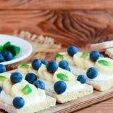 Eigengemaakte zachte kaasroom, bananen en bessensandwiches Low-calorie crackerbrood met bovenste laagjes op houten raad close-up royalty-vrije stock afbeeldingen