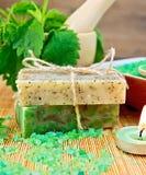 Eigengemaakte zeep en kaars met netels in mortier Stock Afbeelding