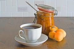 Eigengemaakte zoete organische abrikozenjam in geopende glaskruik met abrikozen en witte kop thee op houten lijst Stock Fotografie