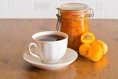 Eigengemaakte zoete organische abrikozenjam in glaskruik met abrikozen en witte kop thee op houten lijst Royalty-vrije Stock Foto