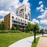 Eigentijds flatgebouw op groen gebied met blauwe hierboven hemel en witte wolken stock afbeeldingen