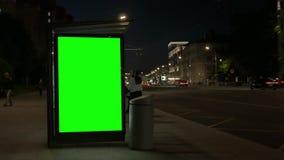 Eigentijdse die bushalte met lichtgevende groene banners wordt uitgerust stock video