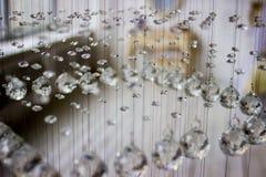 Eigentijdse kristalkroonluchter in ruimtebinnenland Sluit omhoog Kristallen op een koord worden opgeschort dat Crystal Chandelier royalty-vrije stock afbeelding