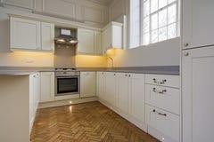 Eigentijdse volledig gepaste keuken in beige stock foto
