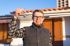 Eigentum, Besitz, neues Haus und Leutekonzept - junger Mann mit den Schlüsseln, die außerhalb des neuen Hauses stehen stockfoto