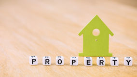 EIGENTUMS-Wort von Würfelbuchstaben vor Symbol des grünen Hauses auf Holzoberfläche Konzept Lizenzfreie Stockfotos