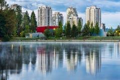 Eigentumswohnungs-Gebäude reflektiert im See mit Bäumen Stockfoto