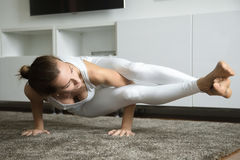 Eight Angle pose. Portrait of a sporty young woman practicing yoga, standing in Eight Angle exercise, Astavakrasana pose, working out, wearing white sportswear Stock Photography