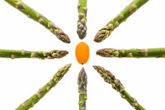 Eight Asparagus Spears Aiming at One Kumquat. Eight green asparagus spears aligned along the vertical, horizontal and diagonal picture axes. All tips are Royalty Free Stock Images