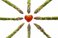 Eight Asparagus Tips Pointing at One Strawberry. Eight green asparagus tips pointing at one heart-shaped strawberry in the middle of the picture Stock Images