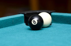 Eight ball in front of cue ball. Eight ball and cue ball on pool table Stock Photos