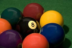 Eight ball in the middle. Of other pool balls on the table Royalty Free Stock Image