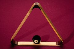 Eight Ball placed within a triangle rack on a pool table. Pool table with rack and placed eight ball Stock Image